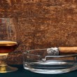 Smoking cigar in an ashtray and glass cognak — Stock Photo