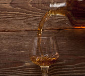 Cognac pour from a bottle in a glass — Stock Photo