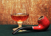 Pipe and a glass of alcohol on green felt — Stock Photo
