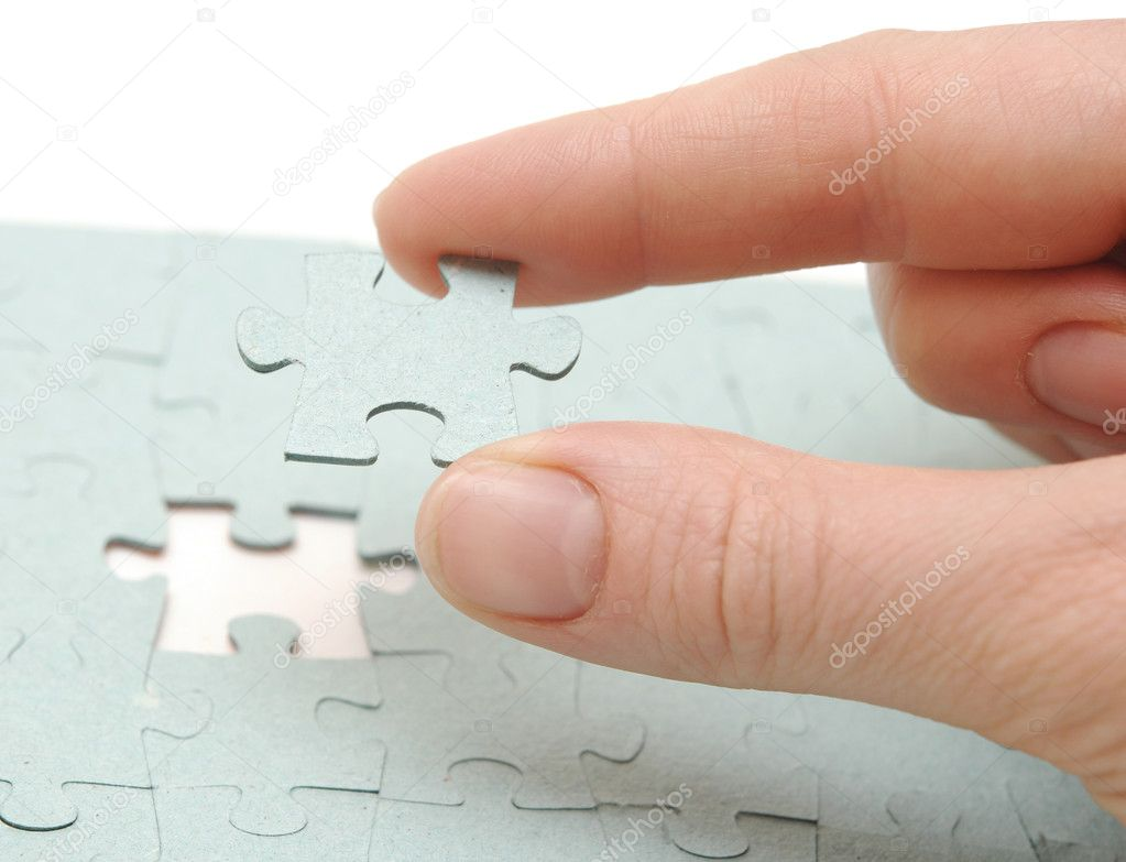 Hand inserting missing piece of jigsaw puzzle into the hole  — Stock Photo #5342614