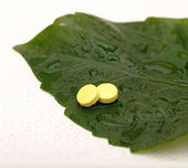 Yellow pill over a wet green leaf — Stock Photo