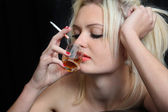 Girl smokes and drinks cognac. — Stock Photo