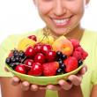 Smiling young woman with bowl full of ripe berries — Stock Photo