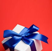 White gift with a blue ribbon on a red background — Stock Photo