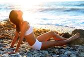 ビーチでの日光浴の美しいブルネット — ストック写真