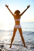Beautiful brunette is happy on the beach — Zdjęcie stockowe