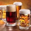 Foto Stock: Cool beer mugs over wooden table.