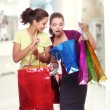 Two friends with shopping. One girl wonders purchases second gir - Stok fotoraf