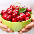 Crockery with cherries in woman hands. — Stock Photo