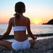 Woman meditating on the beach at sunset. — Stock Photo #4225641