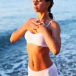 mujer meditando en la playa al atardecer — Foto de Stock