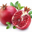 Juicy pomegranate and its half with leaves. — Stock Photo #4226091