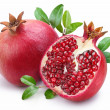 Juicy pomegranate and its half with leaves. — Stock Photo