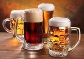 Jarras de cerveza fresca sobre tabla de madera. — Foto de Stock