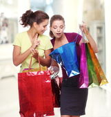 Two friends with shopping. One girl wonders purchases second gir — Zdjęcie stockowe