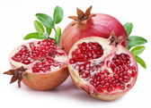Juicy opened pomegranate with leaves. — Stock Photo