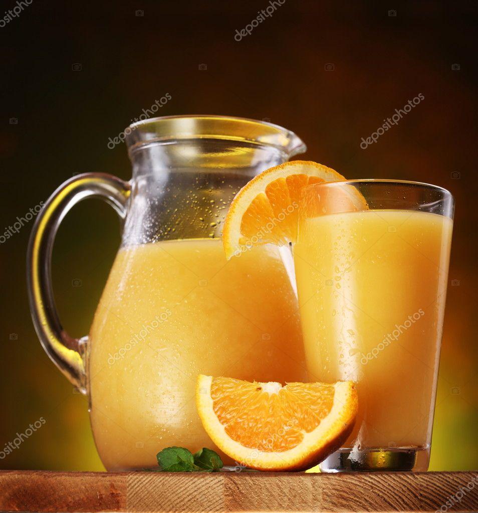 静物: 橘子, 果汁和壶装满了果汁木制的桌子上的玻
