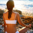 Woman meditating on the beach at sunset. — Stockfoto