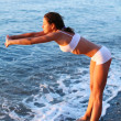 Beautiful brunette doing physical exercises on the beach. — Stock Photo