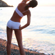 Beautiful brunette doing physical exercises on the beach. - Lizenzfreies Foto