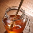 Pot of honey and wooden stick in it. — Stock Photo #4297302