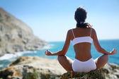 Femme méditant sur un rivage rocheux — Photo