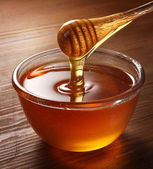 Honey pouring from drizzler into the bowl. — Stock Photo