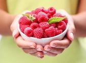 Crockery with raspberries in woman hands. — Stock Photo