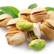 Pistachios with leaves on white background - Stock Photo