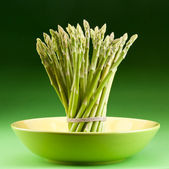 Sheaf of asparagus on a green background. — Stock Photo