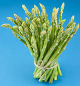 Sheaf of asparagus on a yellow background. — Stock Photo