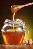 Sweet honey pouring from drizzler into the pot — Stock Photo