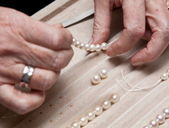 Close hand jeweler stringing pearls on a necklace — Stock Photo