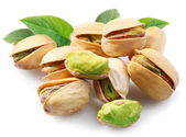 Pistachios with leaves on white background — Stock Photo