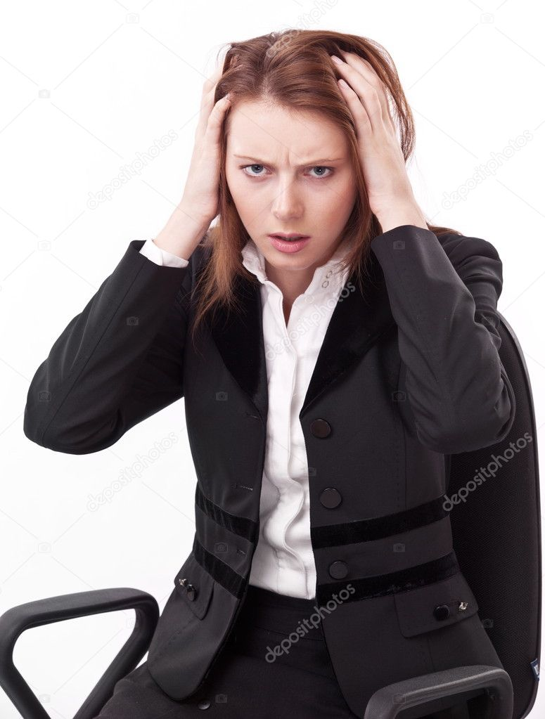 Depressed young woman sitting on a chair, clutches her head.  Stock Photo #4518094