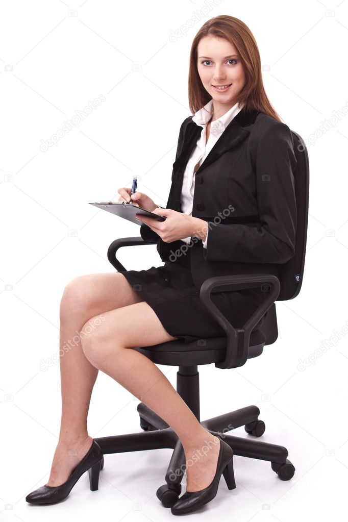 Portrait of young woman sitting on a chair and writiing smth. on paper. Isolated on a white background. — Stock fotografie #4518110