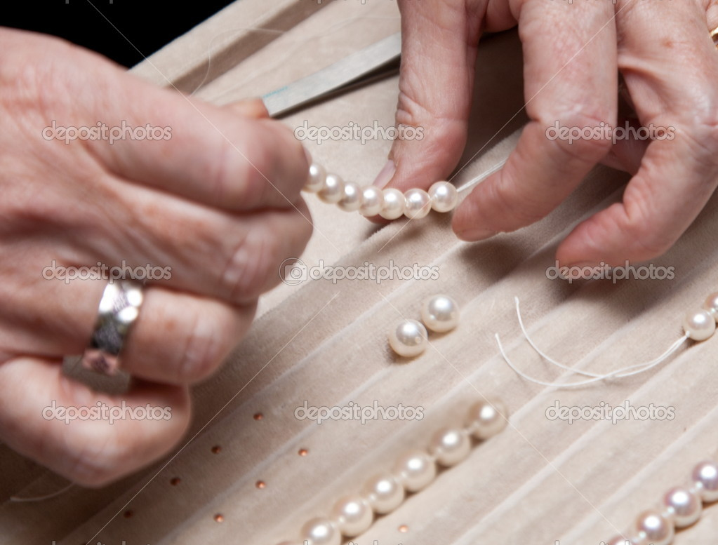 Close hand jeweler stringing pearls on a necklace — Photo #4518851