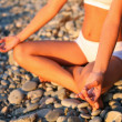 Body of a beautiful girl in a meditation on the beach - 