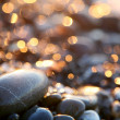Background with sea stones and orange blurred circles. — Foto de Stock