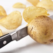 Conceptual image - the knife cuts fresh potatoes and potato chip — Stock Photo