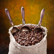 Royalty-Free Stock Photo: Sack of coffee beans and scoop. On a dark background.