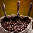 Sack of coffee beans and scoop. On a dark background. — Stock Photo