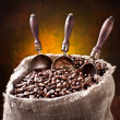 Sack of coffee beans and scoop. On a dark background. — Lizenzfreies Foto