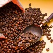 Sack of coffee beans and scoop. On a dark yellow background. — Stock Photo