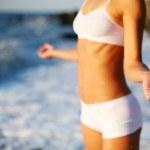 hermosa morena haciendo ejercicios físicos en la playa — Foto de Stock