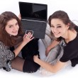 Stock Photo: Two smiling girls with laptop. Isolated on a white background.