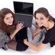 Two smiling girls with laptop. Isolated on a white background. — Stock Photo