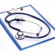 Stock Photo: Medical stethoscope with a clipboard on a white background.