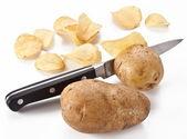 Conceptual image - the knife cuts fresh potatoes and potato chip — Stock Photo