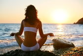 Woman meditating on the beach at sunset. — Stock Photo